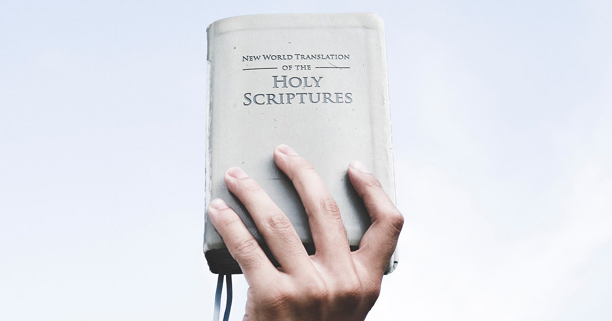 Hand holding a book »New World Translation of the Holy Scriptures«